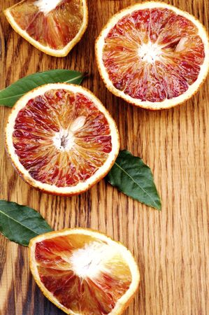 Fresh Ripe Blood Oranges Halves and Slices with Leafs closeup on Wooden background