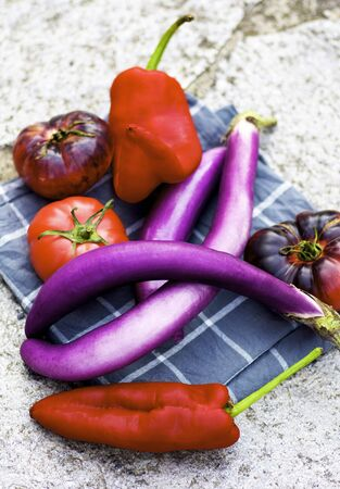 Arrangement of Fresh Ripe Colorful Vegetables with Long Purple Eggplants, Black and Red Tomatoes and Sweet Ramiro Peppers on Napkin closeup on Stone background Foto de archivo