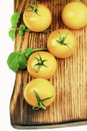Arrangement of Fresh Ripe Yellow Tomatoes with Twigs and Leafs closeup on Wooden board