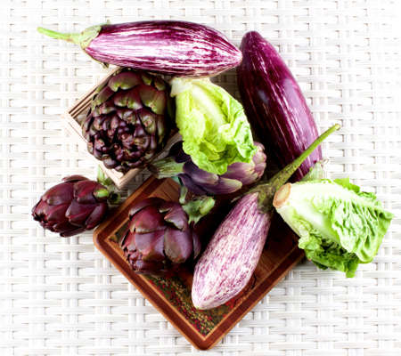 Fresh Mediterranean Vegetables with Crunchy Romaine Lettuce, Striped Eggplants and Artichokes closeup on Wicker background