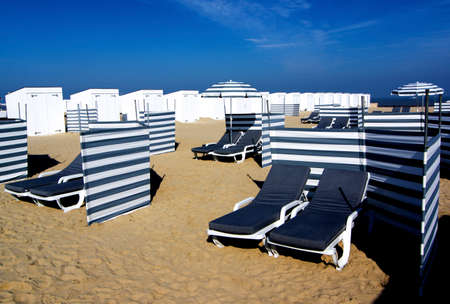 Sand Beach with Striped Sun Umbrellas, Loungers and Partitions for Social Distancing over Blue Sky background