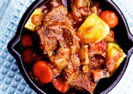 Delicious Slow Cooked Beef Stew with Carrots, Potatoes, Celery and Leek in Cast Iron closeup on Blue Napkin. Top View Foto de archivo