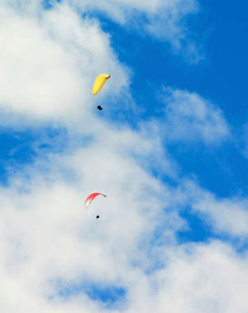Two Parachute Wings in White Fluffy Clouds Sky in Sunny Day Foto de archivo