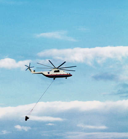Firefighters Helicopter in Flight with Water Basket against Evening Blue Sky Foto de archivo