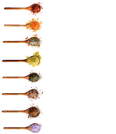 Collection of Various Colorful Spices in Wooden Spoons In a Row: Dried Paprika, Curry Powder, Salt with Petals, Chili and Cayenne Pepper, Cumin Powder, Thyme, Coriander