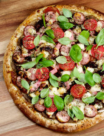 Delicious Homemade Pizza with Sausages, Mozzarella Cheese, Cherry Tomatoes and Basil Leaves Cross Section on Wooden background