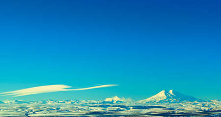 Two Beautiful Snowy Mountain Peaks of Caucasus Range and Flying Cloud against Blue Sky in Sunny Winter Day Outdoors