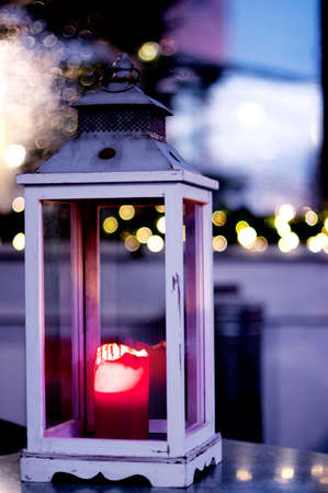 Christmas Decoration with Candle Wooden Lantern against Blurred Garland Lights on Dusk Outdoors