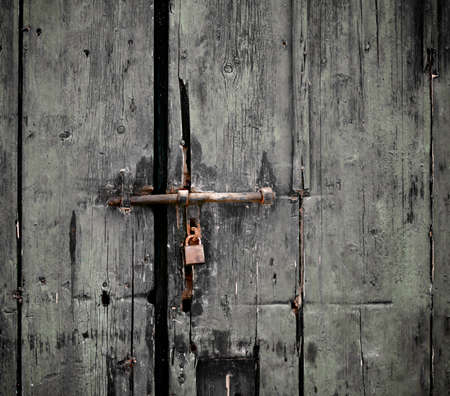 Old Gray Cracked Wooden Door with Rusty Barn Lock closeup Outdoors
