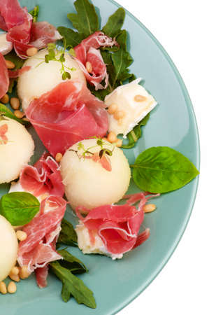 Delicious Prosciutto with Melon Balls, Basil, White Cheese, Pine Nuts and Microgreens on Green Plate closeup on White background