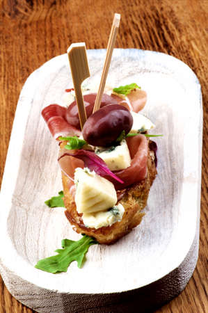 Delicious Spanish Tapas with Rochefort Cheese, Red Olives and Jamon with Greens closeup on White Wooden Plate on Wooden background Foto de archivo
