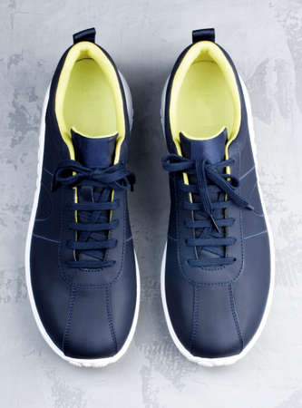 Dark Blue Contemporary Leather Sneakers with Yellow Liner closeup on Gray Grunge background