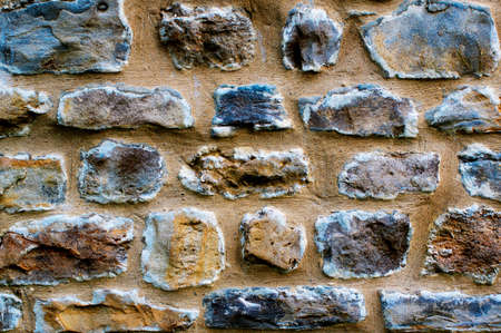 Background of Variegated Ancient Stone Wall with Sand and Concrete closeup