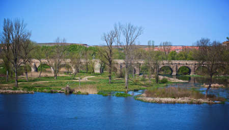 Stone Arched Roman Bridge over Tormes River in Spring Sunny Day. Salamanca, Spain