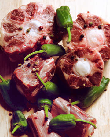 Fresh Raw Bull Oxtails with Pimiento Peppers closeup on Wooden background. Selective Focus