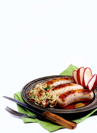 Delicious Grilled White Munich Sausages with Pickled Cabbage, Chopped Radish on Green Napkin isolated on White background