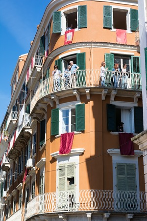smashing: CORFU, GREECE - APRIL 30, 2016: Buildings with red banners on balconies in anticipation of the Resurrection on the morning of Holy Saturday. Easter pot smashing. Editorial