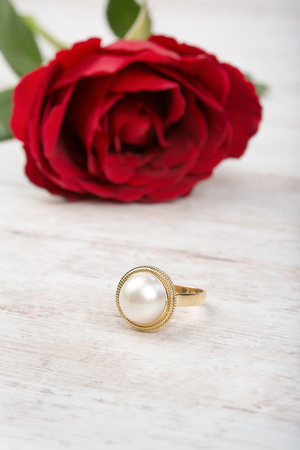 Red rose and golden pearl ring on white wooden background