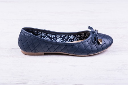 Dark blue ladies flat shoe on white wooden background Stock Photo