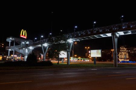 BURGAS, BULGARIA - FEBRUARY 1, 2018: Overhead pedestrian bridge at night. McDonalds restaurant.