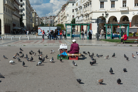 THESSALONIKI, GREECE - MAY 29, 2017: Famous Aristotelous square in Thessaloniki, Greece. Woman selling seeds for feeding the pigeons. Thessaloniki is the second largest city in Greece.