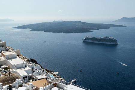 White houses of Fira, Santorini and Nea Kameni volcano in the background
