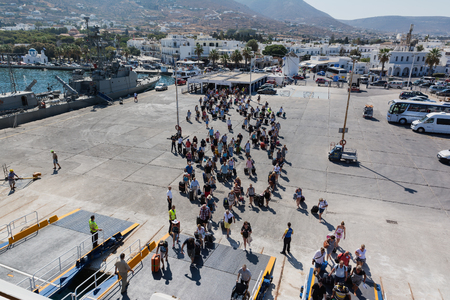 PAROS, GREECE - SEPTEMBER 17, 2016: Passengers and cars embark on a ship at the port of Paros in Greece. Paros is a beautiful Cycladic island visited by many tourists every year.
