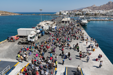NAXOS, GREECE - SEPTEMBER 17, 2016: Passengers and cars disembark from a ship at the port of Naxos in Greece. Naxos is a beautiful Cycladic island visited by many tourists every year.