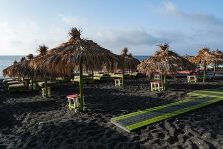 Tanning beds and straw umbrellas on Perissa beach, Santorini island, Greece Stock Photo