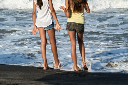 Nice legs of a pretty girl in jeans shorts standing in water. Close-up view of girlss legs on the beach