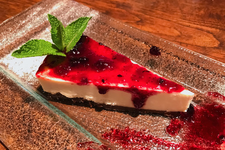 Slice of cheesecake with cranberry jam on glass plate decorated with mint leaf.