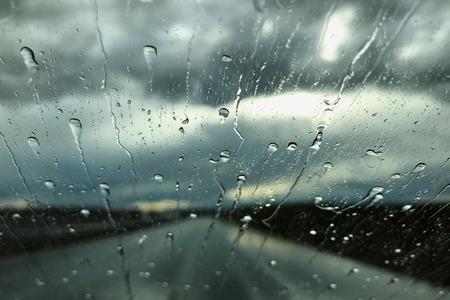 Rain drops on a car windshield. Rainy day view through a car window. Rainy season concept.
