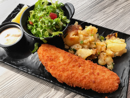 Breaded white fish with potatoes and fresh lettuce salad.