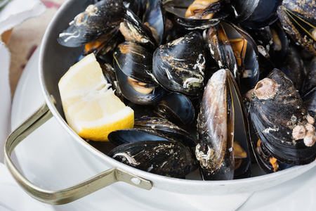 Boiled mussels in shells with lemon. Shellfish food. Stock Photo