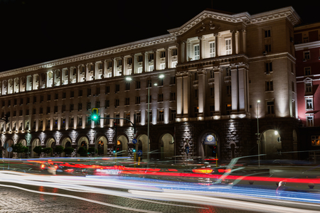 Building of Council of Ministers in Sofia, Bulgaria. Night view with traffic light trails. Text Council of ministers in Bulgarian on the building.