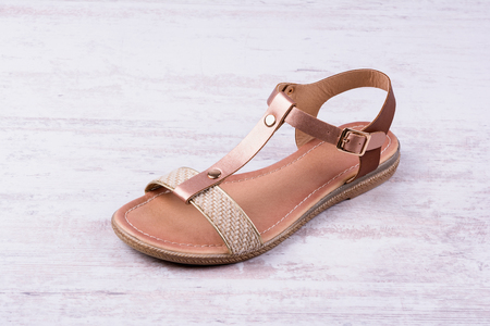 Womens sandal on white wooden background.