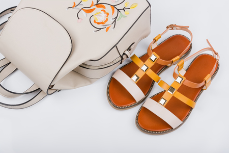 Fashionable womens sandals and backpack on white background.