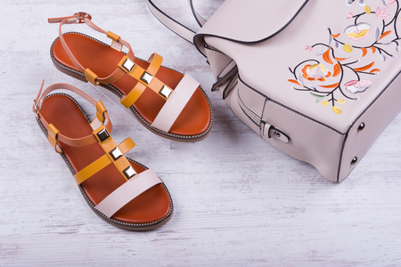 Fashionable womens sandals and backpack on white wooden background.