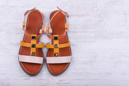 Pair of womens sandals on white wooden background.