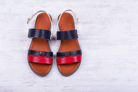 Pair of fashionable womens sandals on white wooden background.