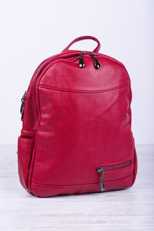 Red leather fashionable female backpack on white wooden background.