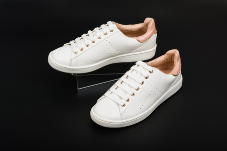 Womens sport leather shoes on black background.