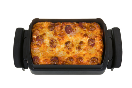 Homemade pizza with salami, bacon, tomato sauce, yellow cheese, mozzarella in a baking dish isolated on white background.