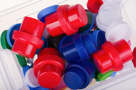 Colorful plastic lids in a box on white background.