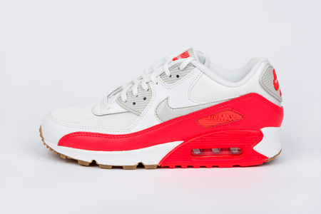 BURGAS, BULGARIA - AUGUST 30, 2016: Nike Air MAX women's shoes - sneakers - trainers in white and orange on white background. Nike is a global sports clothes and running shoes retailer. Editorial