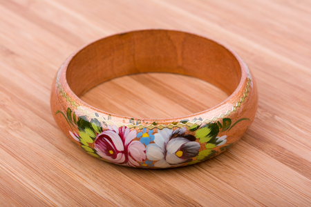 Colorful russian wooden bracelet on wooden background.