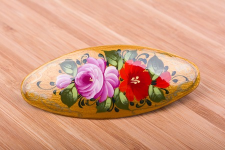 Colorful russian wooden hair clip on wooden background.