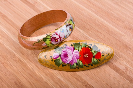 Colorful russian wooden bracelet and hair clip on wooden background.