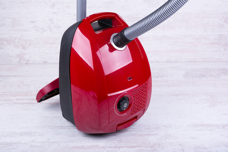 Red vacuum cleaner on white wooden background.