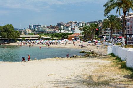 KUSADASI, TURKEY - AUGUST 20, 2017: Beautiful sand beach of Kusadasi with colorful straw umbrellas and lounge chairs, Aegean Sea,Turkey.